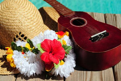 Ukulele and straw hat and lei on dock next to water